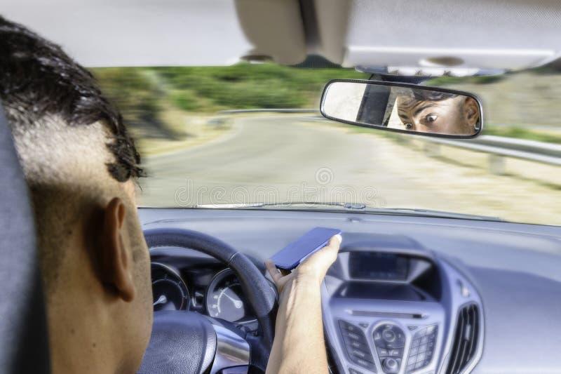 年轻司机,使用智能手机,在汽车的路 免版税库存照片