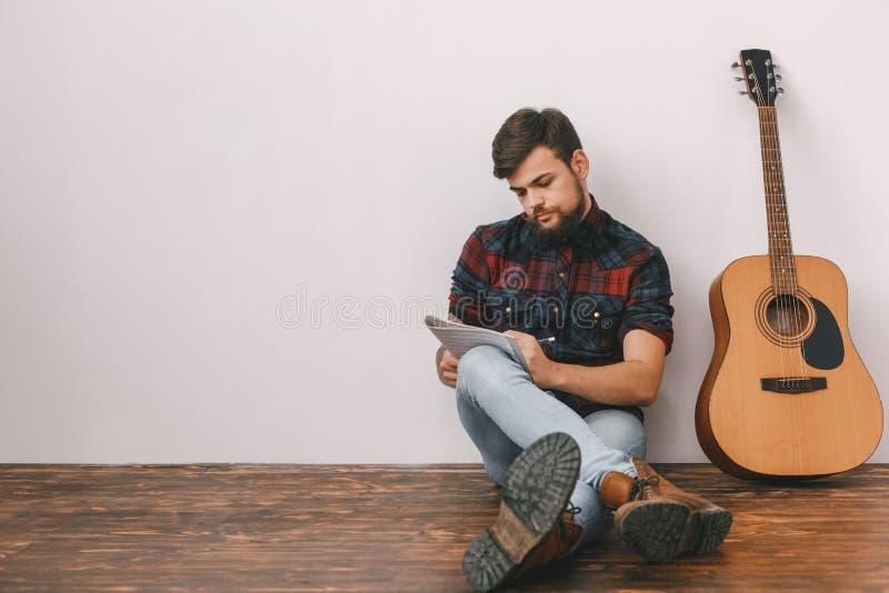 年轻吉他弹奏者行家在家有吉他坐的文字曲调的 免版税库存照片