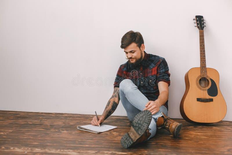 年轻吉他弹奏者行家在家有吉他坐的文字歌曲的 库存图片