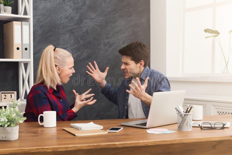 年轻同事夫妇争论在办公室 免版税库存图片