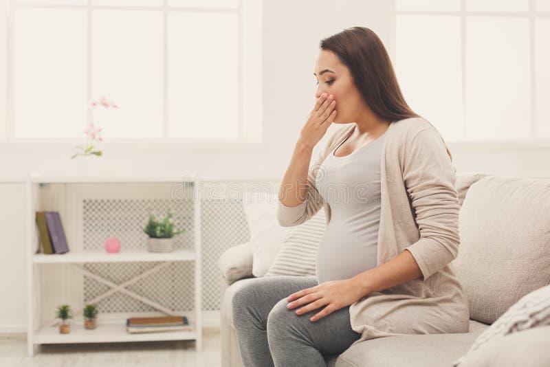 年轻呕吐的妇女坐沙发 库存图片