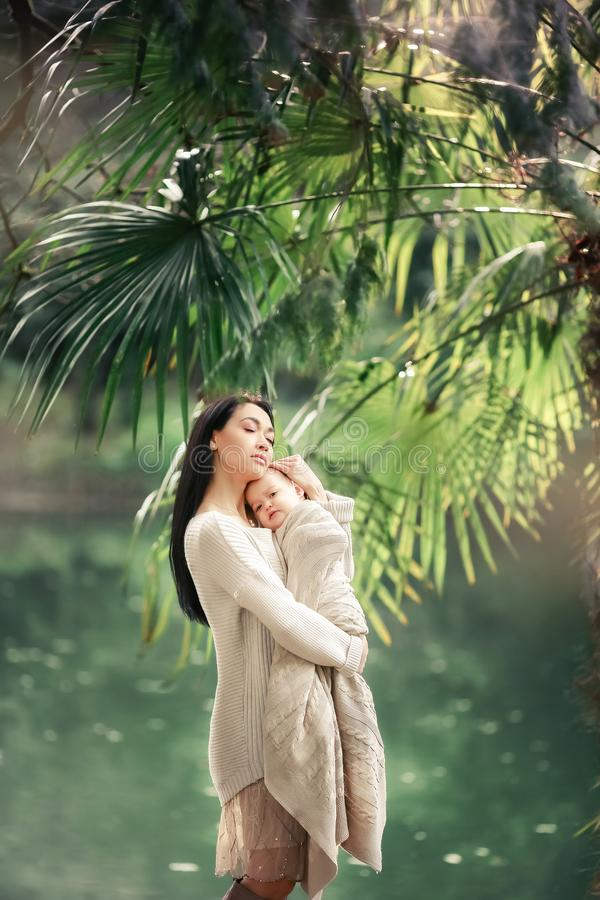 年轻和愉快的母亲喜欢她的年轻儿子和步行沿湖的岸在夏天在公园 库存照片