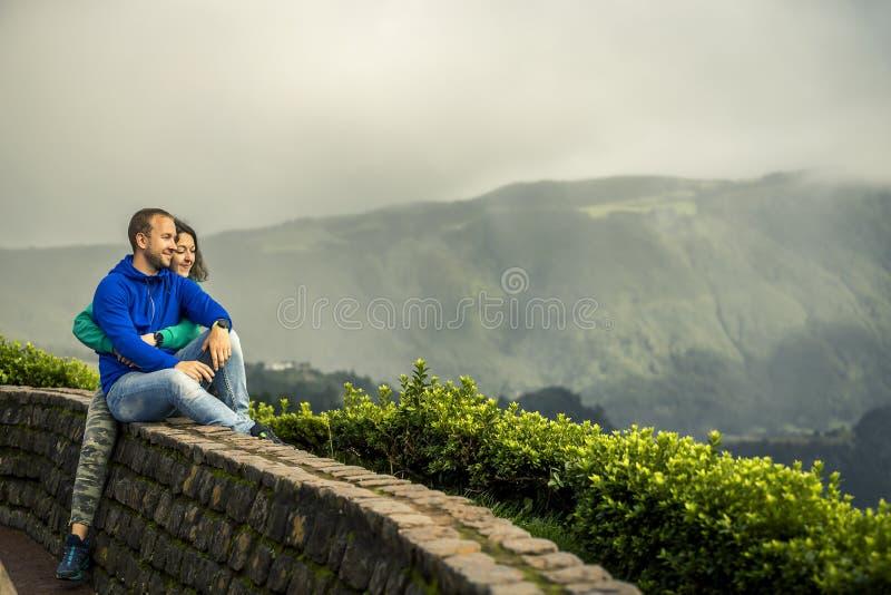 年轻和有吸引力的夫妇是拥抱和坐在观点边缘 免版税库存照片