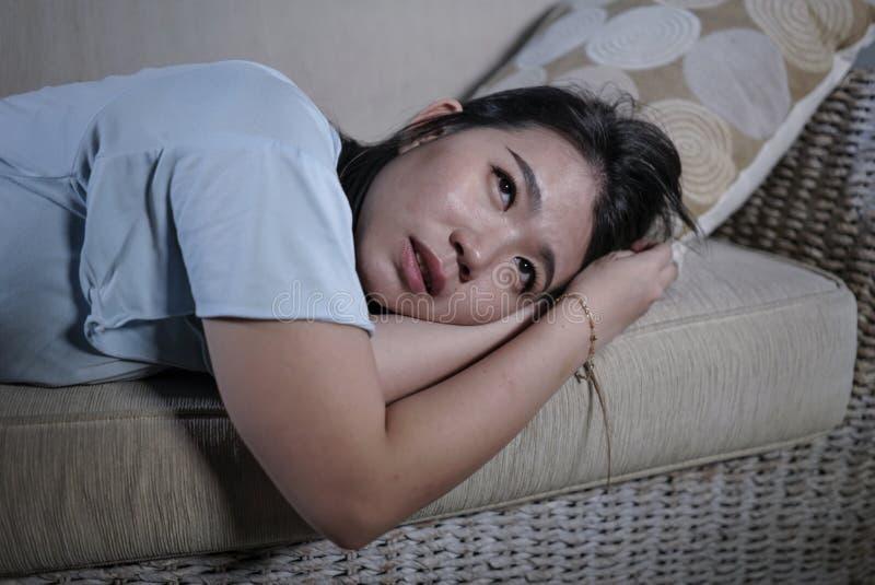 年轻哀伤和沮丧的亚裔日本妇女哭泣的绝望开会在家沙发长沙发遭受的消沉问题和忧虑 免版税库存照片