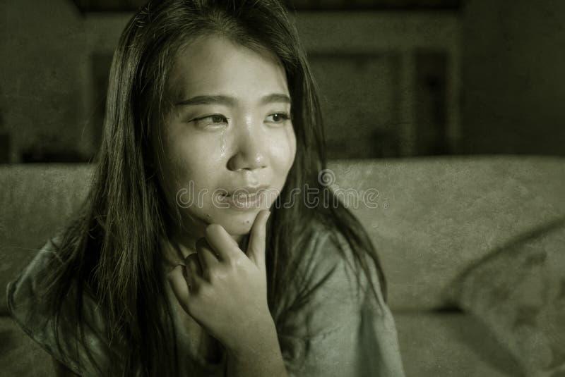 年轻哀伤和沮丧的亚裔日本妇女哭泣的绝望开会在家沙发长沙发遭受的消沉问题和忧虑 库存图片