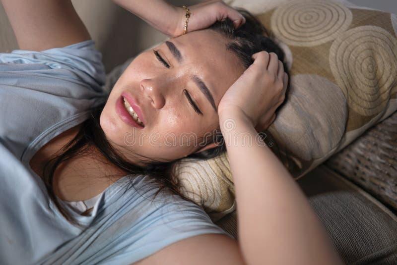 年轻哀伤和沮丧的亚裔日本妇女哭泣的绝望开会在家沙发长沙发遭受的消沉问题和忧虑 免版税库存图片
