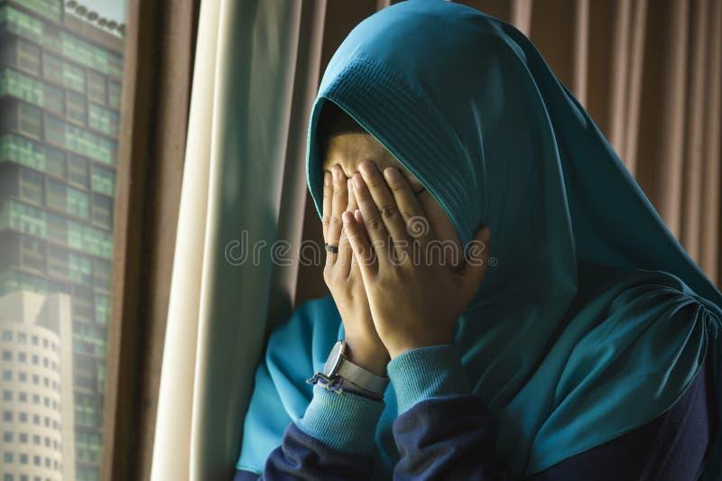 年轻哀伤和沮丧的回教妇女在感觉不适的遭受的消沉的回教传统Hijab头围巾在家窗口里 免版税库存图片