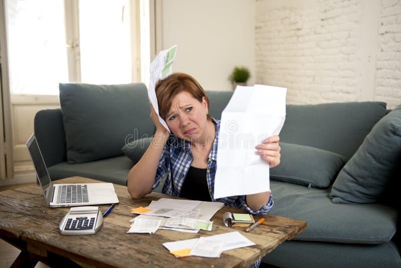 年轻哀伤的担心和绝望妇女银行业务和会计家庭月度和信用卡费用与计算机膝上型计算机 免版税图库摄影