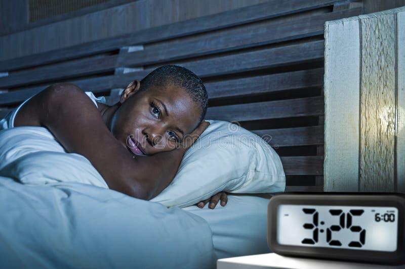 年轻哀伤的沮丧的黑人美国黑人的妇女醒在丙氨酸的床失眠的遭受的失眠失眠忧虑问题 库存图片