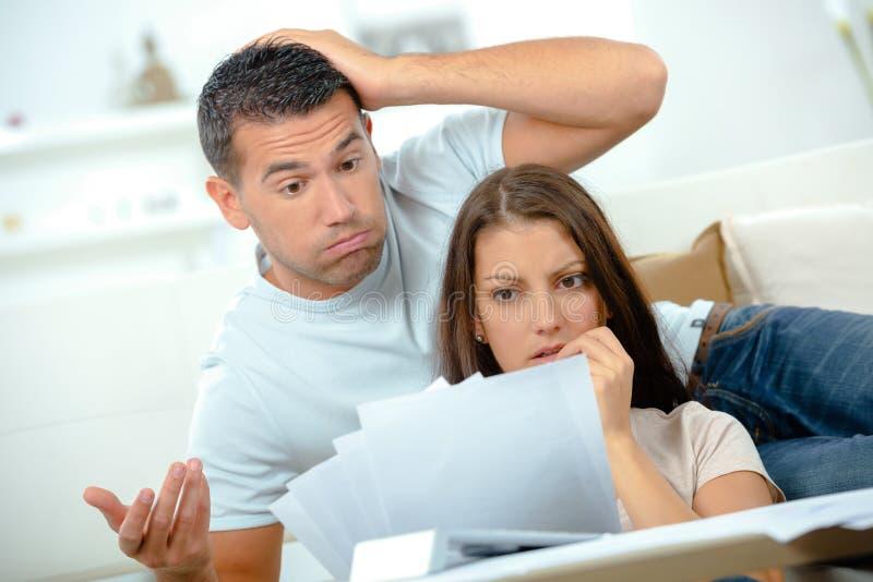 年轻哀伤的couplecalculating的月度费用 免版税库存照片