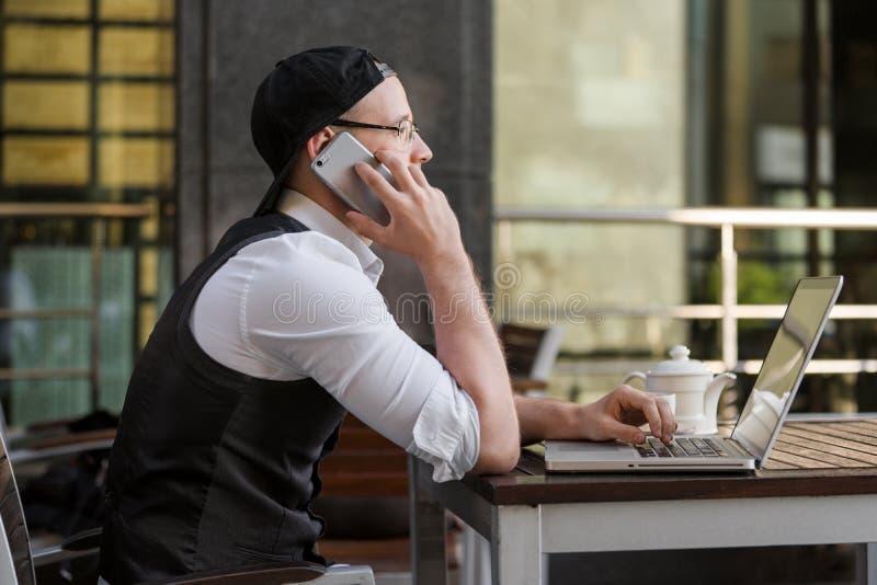 年轻商人与膝上型计算机和电话一起使用在室外咖啡馆 库存照片