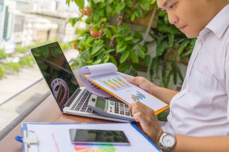 年轻商人与计算器和财政报告一起使用 库存照片