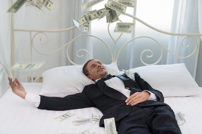 年轻商人以愉快,在床上的微笑 谁是successf 库存图片