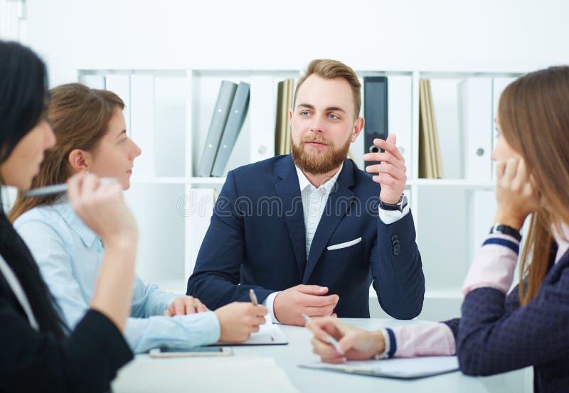 年轻商人在一个会议在办公室 年轻创造性的工友与在现代的新的起始的项目一起使用 免版税库存图片