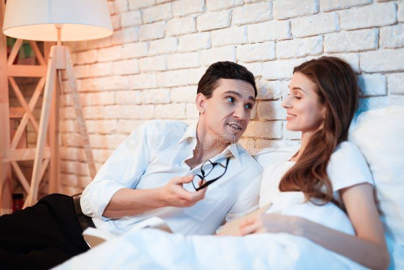 年轻商人在床上读书与白人妇女 年轻夫妇长沙发谈论事务 免版税库存图片