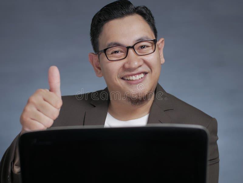 年轻商人在笔记本电脑上工作,微笑着 免版税库存照片