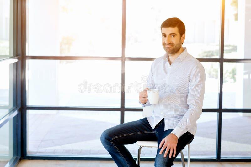 年轻商人坐一把凳子在办公室 库存图片