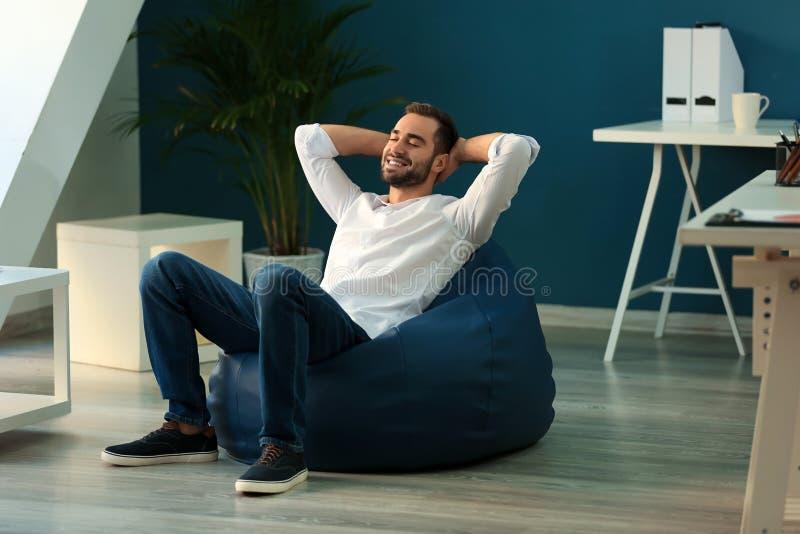 年轻商人坐装豆子小布袋椅子在办公室 免版税库存照片