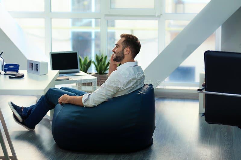 年轻商人坐装豆子小布袋椅子在办公室 免版税库存图片