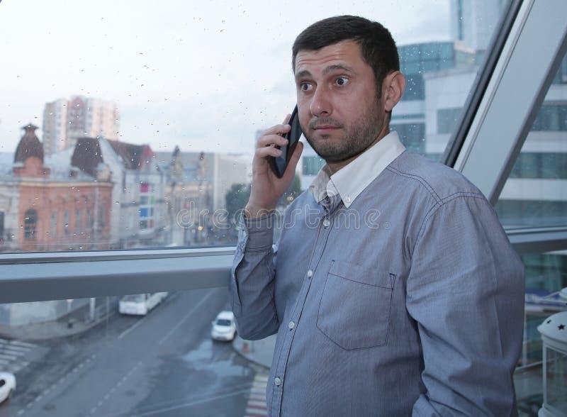 年轻商人情感地谈话在充满惊讶的一个手机在他的面孔以一个全景窗口为背景 库存照片