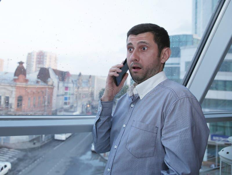 年轻商人情感地谈话在充满惊讶的一个手机在他的面孔以一个全景窗口为背景 免版税库存图片