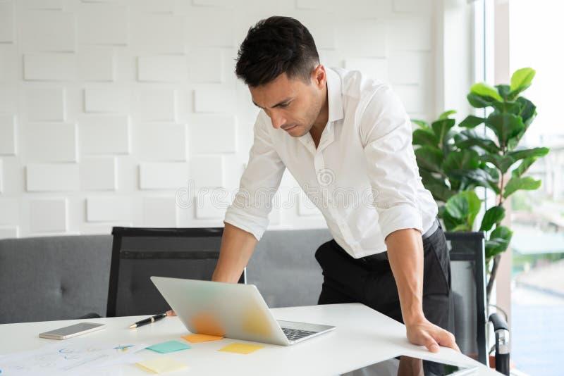 年轻商人是站立和看膝上型计算机 免版税库存图片