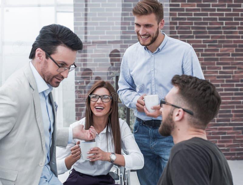 年轻商人是谈话和微笑在咖啡休息期间在办公室 免版税库存图片