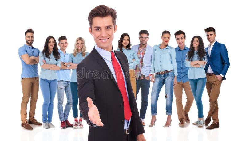 年轻商人欢迎您到他的与握手的队 免版税库存图片