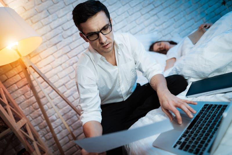 年轻商人看纸片 人研究膝上型计算机 免版税库存照片