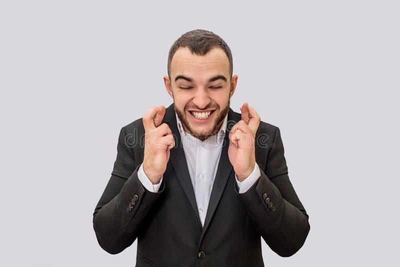 年轻商人站立并且保持但愿 他收缩并且微笑 背景查出的白色 免版税库存照片