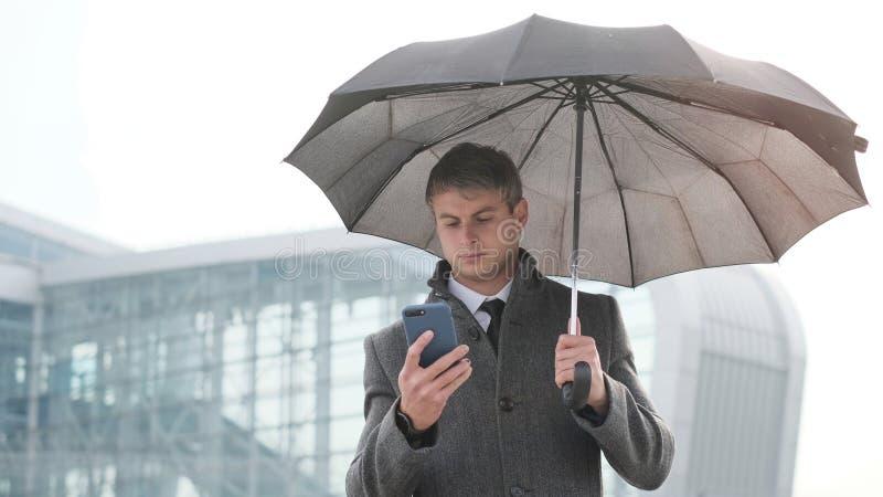 年轻商人藏品伞和使用智能手机在a 库存图片