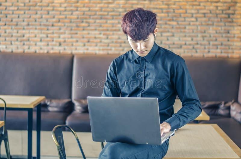 年轻商人读书从有一个严肃的表示的一台手扶的片剂计算机,他坐栖息在桌边缘 免版税库存图片