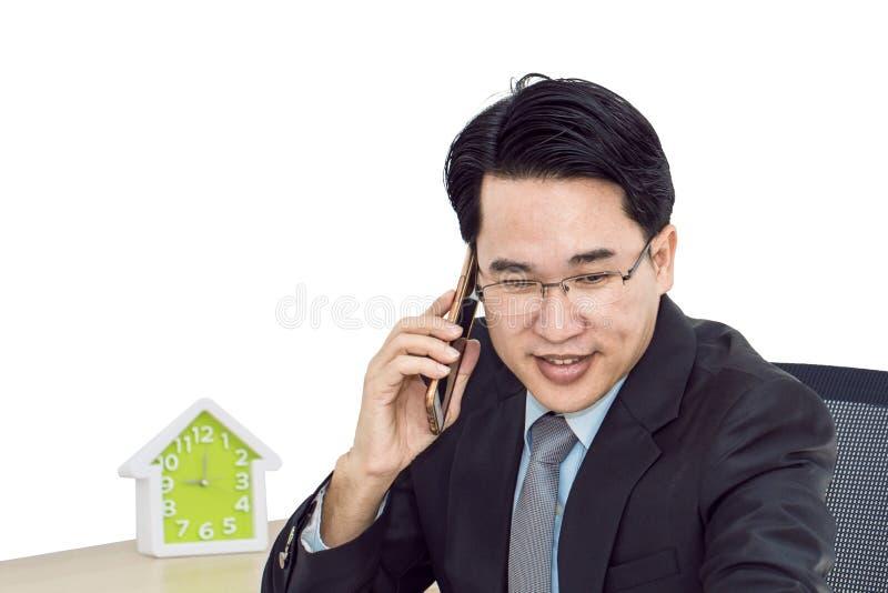 年轻商人谈话与巧妙的电话 他看起来微笑 免版税库存照片