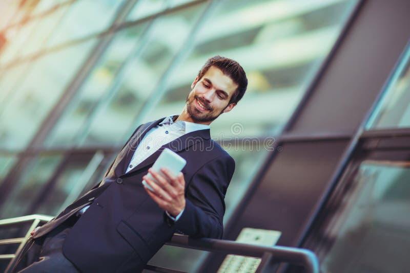 年轻商人谈话在他的电话户外 库存图片