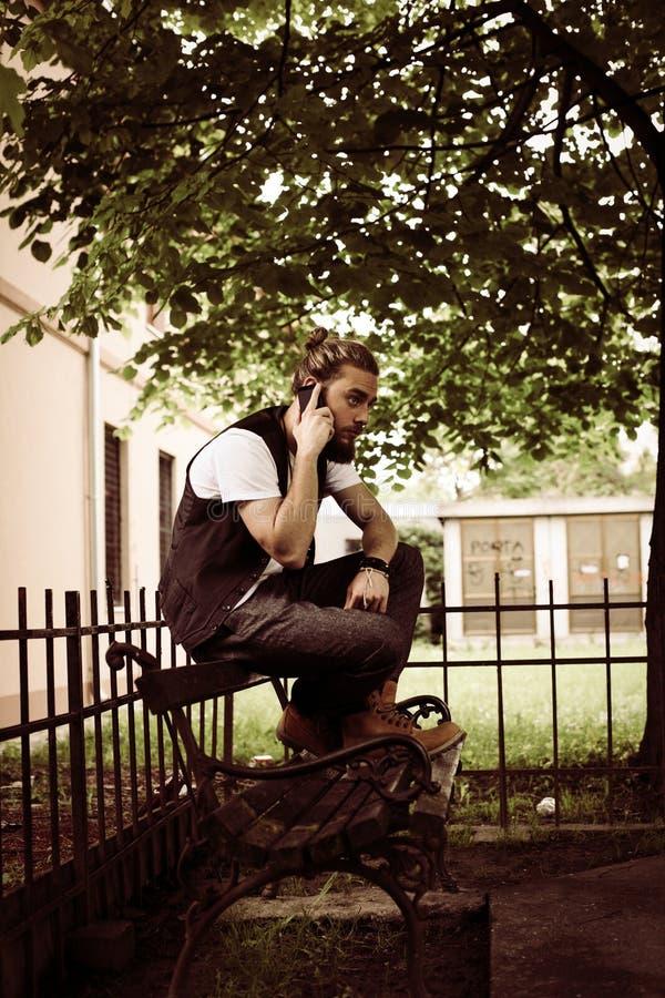 年轻商人谈话在手机在公园 免版税库存图片