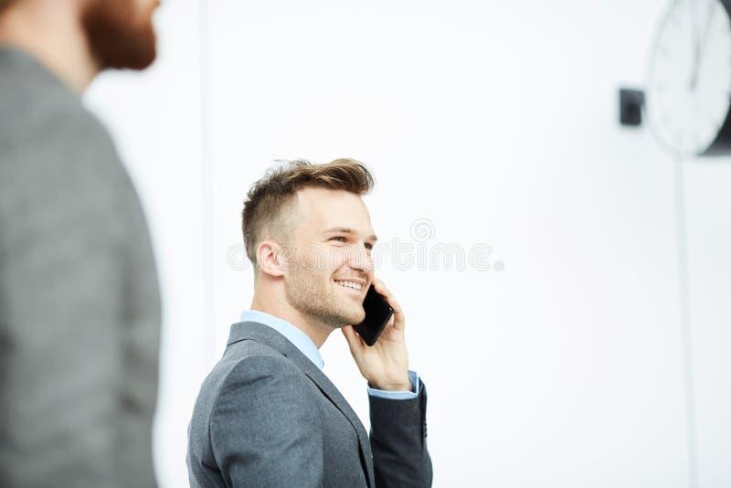 年轻商人谈话在电话,当走时 免版税库存图片