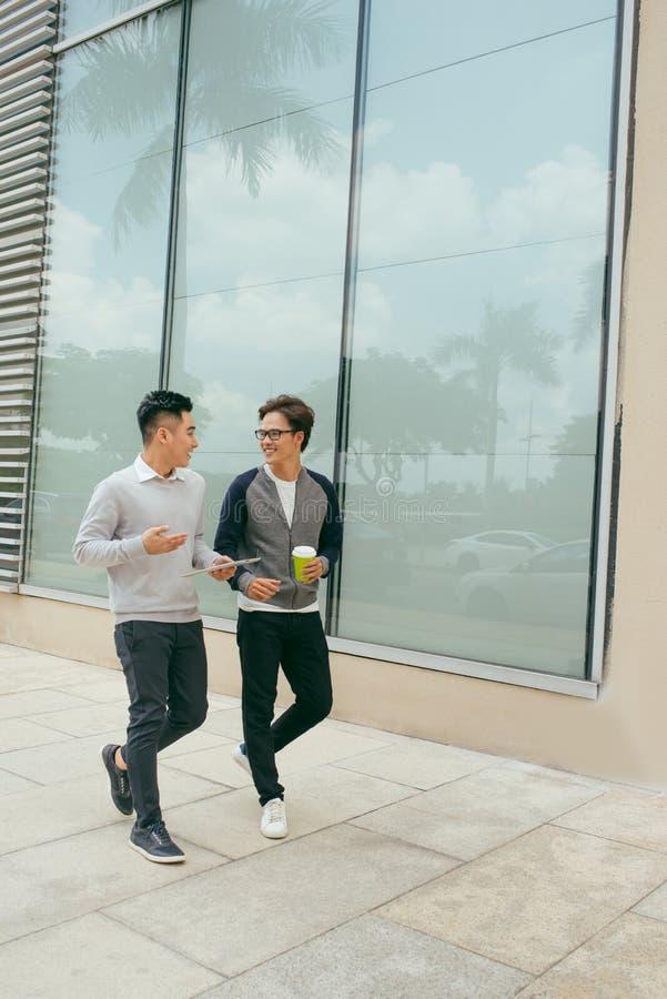 年轻商人走并且放松微笑有城市背景 免版税库存照片