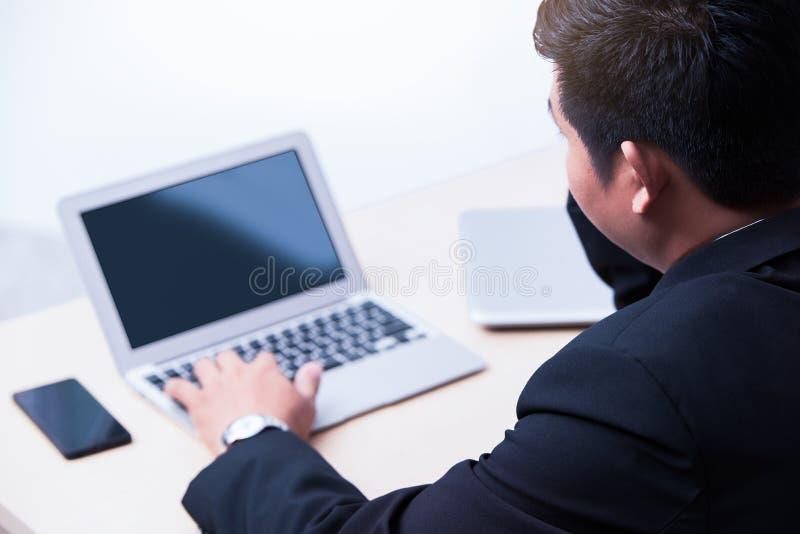 年轻商人键入的膝上型计算机 图库摄影