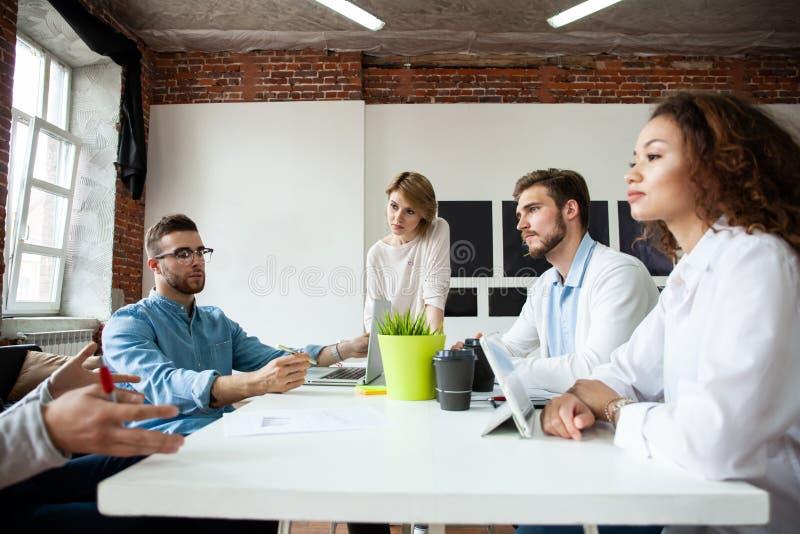 年轻商务伙伴分享和谈论想法在会议上在办公室 免版税库存照片