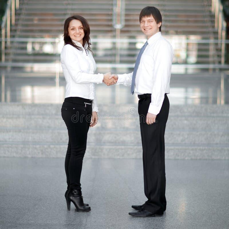 年轻商务伙伴受欢迎的握手办公室的背景的 库存图片