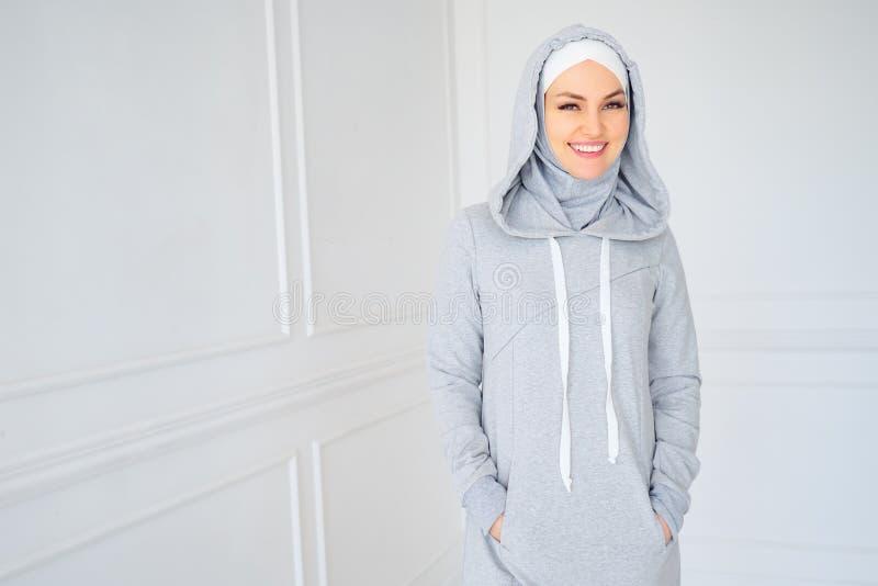 年轻回教妇女画象灰色hijab和全国健身礼服的在家 免版税库存照片