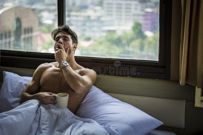 年轻困人,在打呵欠的床上 库存图片
