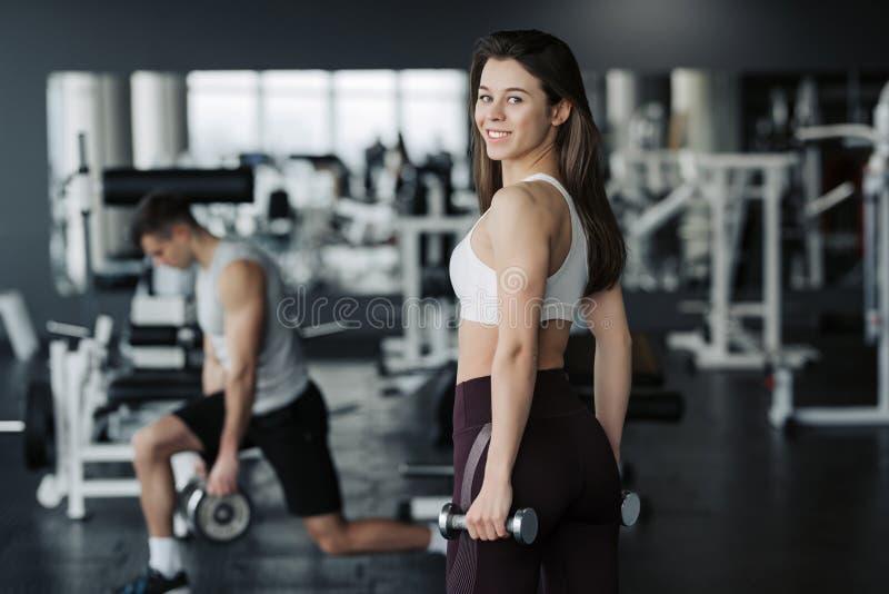 年轻在健身房佩带的运动服的女运动员举的重量有她的背景的男朋友的 库存照片