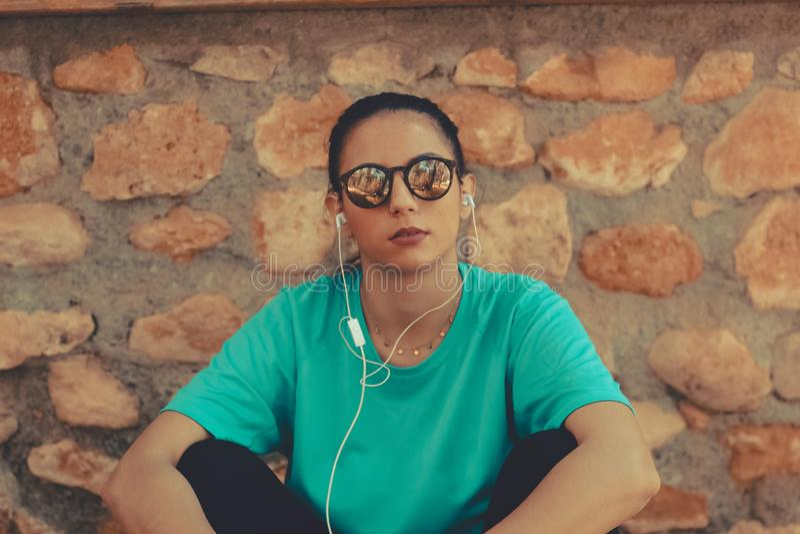 年轻在奔跑以后的美女坐的和听的音乐 免版税库存图片