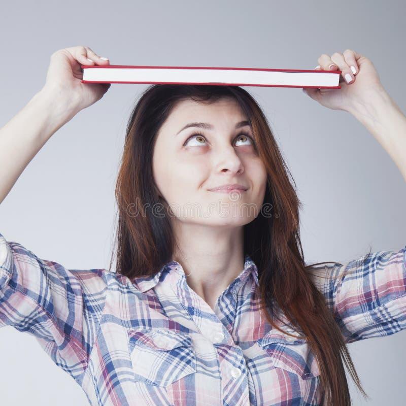 年轻在她的头的学生女孩分类帐余额簿 免版税库存照片