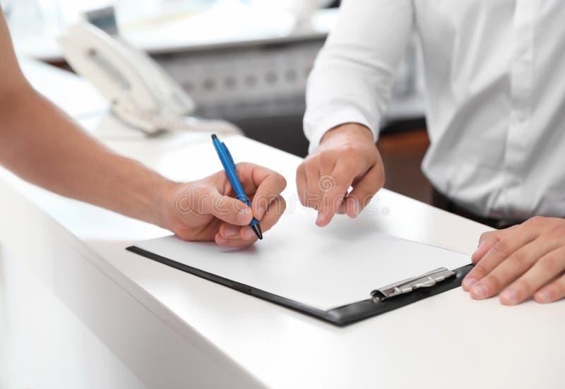 年轻在沙龙的人签署的文件 免版税图库摄影