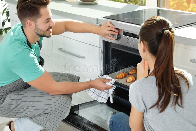 年轻在烤箱的夫妇烘烤的新月形面包 库存图片