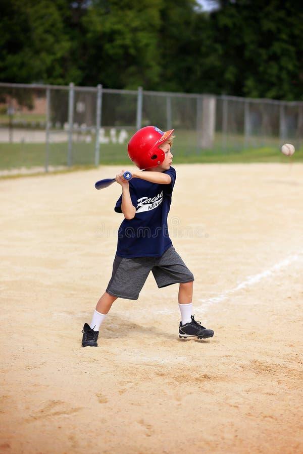 年轻在球的男孩摇摆的棒球棒在青年Ragball比赛 库存照片