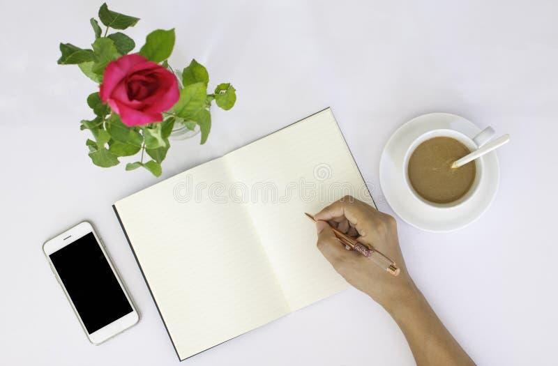 年轻在空白的笔记本的人右手文字 免版税图库摄影