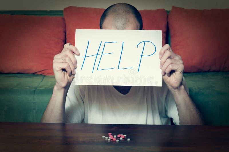 年轻在纸的人藏品帮助标志书面信与在他前面的强的药剂药片上瘾者自杀的概念 图库摄影